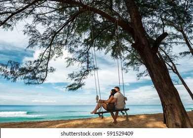 Couple in love on a swing by the sea. Couple in love on an island off the coast. Honeymoon. Couple by the sea. A guy and a girl travel to beautiful places. Honeymoon trip. Relax on the island