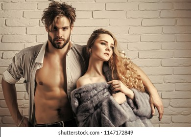 Couple in love on white brick wall. Woman in mink fur coat and man in open shirt. Girl with long blond hair and macho with six pack, ab. Fashion, style, winter clothing concept