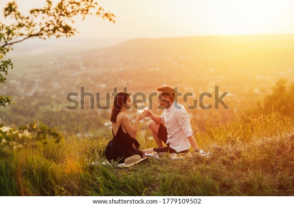 Couple in love on a white plaid take a picnic against the backdrop of a sunset in the mountains. Romantic time. Beautiful couple is enjoying picnic time at sunset.  Copy space.