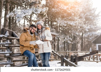 Couple in love on a winter vacation looking at photos taken with their tablet computer outdoors on a sunny, snowy day