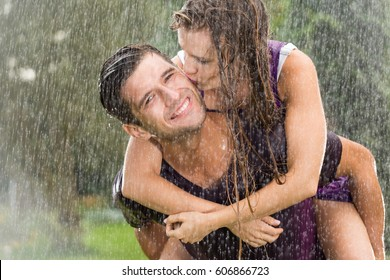 Couple in love playing in the summer rain