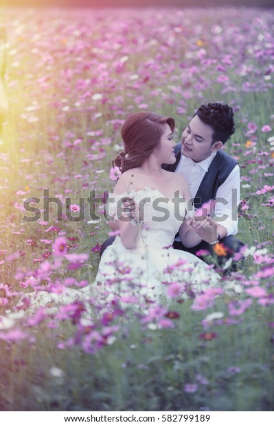 couple in love. portrait of asia young stylish fashion couple posing on outdoor. wedding style, flare and vintage effect