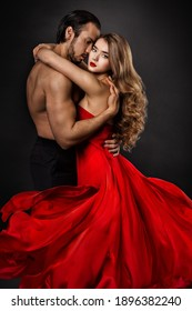 Couple in Love Portrait. Athletic Man Kissing and Embracing Romantic Woman in Red Flying Dress. Black Background