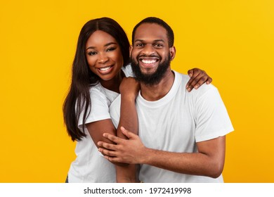 Couple In Love. Portrait of joyful black sweethearts hugging and posing to camera, standing together isolated over yellow background in studio, copy space. Casual guy and lady smiling