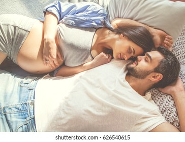 Couple in love pregnant lie in bed cuddling, waiting for baby