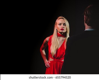 couple in love of pretty blonde woman in red dress and lip makeup, handsome man or businessman in outfit on black background