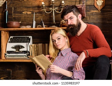 Couple in love reading poetry in warm atmosphere. Lady and man with beard on dreamy faces with book, reading romantic poetry. Romantic evening concept. Couple in wooden vintage interior enjoy poetry.