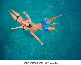 Couple in love refreshing in the ocean on vacation. They are floating on the surface. Wide angle selfie shot with selfie stick.