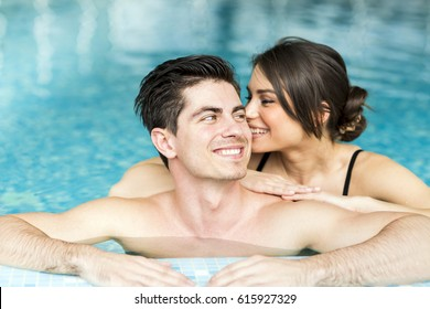 Couple in love relaxing by the side of the swimming pool