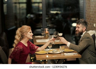 Couple in love at the restaurant. Proposal and anniversary. Valentines day with sexy woman and bearded man. Date of family couple in romantic relations, love. Business meeting of man and woman.