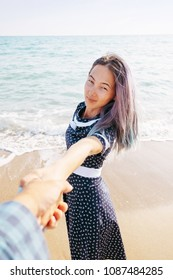 Couple in love resting on beach summer vacations. Beautiful young woman holding man's hand and leading him on sea, point of view shot.