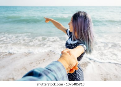 Couple in love resting on summer vacations. Beautiful young woman holding man's hand and pointing at sea, point of view shot. Focus on male hand.