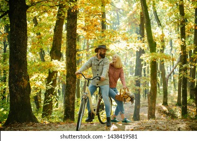 Couple in love ride bicycle together in forest park. Romantic date with bicycle. Bearded man and woman relaxing in autumn forest. Romantic couple on date. Date and love. Autumn date hike in forest.