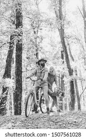 Couple in love ride bicycle together in forest park. Bearded man and woman relaxing in autumn forest. Romantic couple on date. Date and love. Autumn date hike in forest. Romantic date with bicycle.