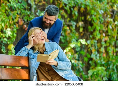 Couple in love romantic date nature park background. Girl sit bench read book while wait boyfriend. Wait him for date. Dating in park. Romantic relations concept. Park best place for romantic date.