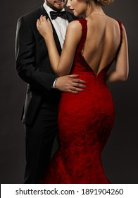 Couple in Love. Romantic Fashion Glamour Woman in red Dress and Elegant Man in Suit. Black Studio Background