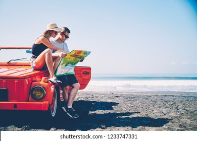 Couple in love searching route for roadtrip spending summer vacation together renting vintage cabriolet,male and female hipsters traveling by automobile on tropical island talking about sightseeing