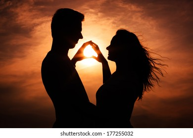 Couple in love silhouette during sunset - touching hands