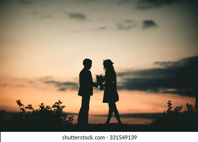 Couple in love silhouette during sunset - A Young couple in love outdoor at the sunset - man gives flowers