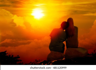 couple in love sit on the mountain looking the sunrise together