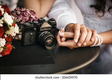Couple in love sitting in cafe, holding each other's hand. Concept photo about male and female's hands, love and old photo camera. Focused on hands and camera. Shallow depth of field.