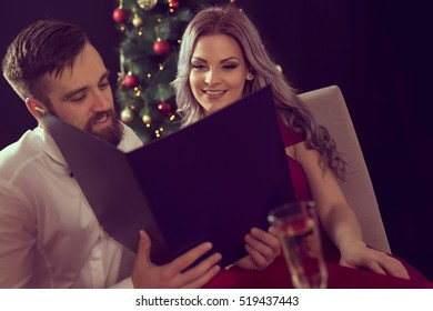 Couple in love sitting at a dinner table, holding a menu and taking an order. Christmas tree in the background, focus on the girl.