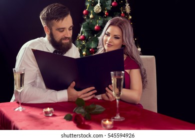 Couple in love sitting at a dinner table, holding a menu and taking an order. Christmas tree in the background, focus on the girl