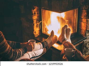 Couple in love sitting near fireplace. Legs in warm socks close up image. Cozy Christmas Home atmosphere