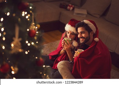 Couple in love sitting next to a Christmas tree, wearing Santa hats, drinking hot tea and exchanging presents. Focus on the woman