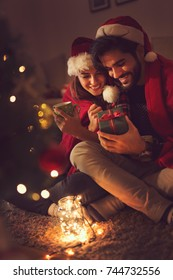 Couple in love sitting next to a Christmas tree, wearing Santa's hats, drinking hot tea and exchanging presents. Selective focus