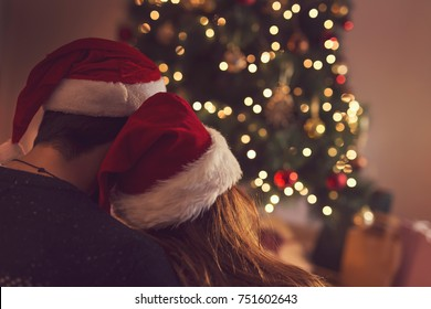 Couple in love sitting next to a Christmas tree, wearing Santa's hats, hugging and looking away from the camera towards the tree. Selective focus on the girl's hat