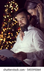 Couple in love sitting next to a nicely decorated Christmas tree, looking at some photos on a tablet computer. Focus on the guy