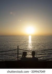 couple in love ,sitting on the bench and watching sunset on the sea,romantic and love background