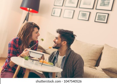 Couple in love sitting on a living room floor, having a conversation and dipping fruit into melted chocolate