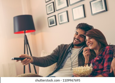 Couple in love sitting on a living room sofa, watching TV and eating popcorn. Focus on the man