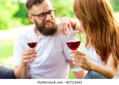 Couple in love sitting on a picnic blanket in a park holding glasses of wine and making a toast. Focus on the hand