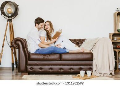 couple in love sitting on the sofa and reading a book