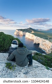Couple in love sitting on a viewpoint enjoiing sunset over the sea at capo caccia sardinia