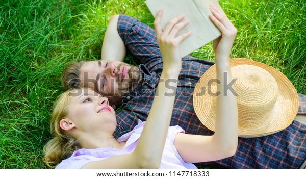 Couple in love spend leisure reading book. Couple soulmates at romantic date. Romantic couple students enjoy leisure with poetry or literature grass background. Man and girl lay on grass having fun.