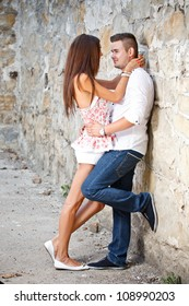 Couple in love standing in front of a stone wall