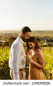 Couple in love standing in a vineyard laughing together. Smiling woman on a date holding a glass of wine standing with her boyfriend at a wine farm.