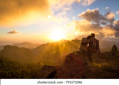 couple in love at the summit of roque nublo look at the sunset. Travel backpacking in gran canaria