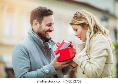 Couple in love.Man surprising his girlfriend with a gift.