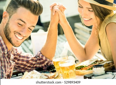 Couple in love taking selfie at beer bar on travel excursion - Young happy tourists enjoying happiness moment at street food restaurant - Relationship concept with soft focus and desat contrast filter