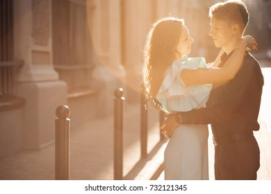 Couple in love. Tenderness and embrace. The guy and the girl look into each other's eyes in the sunset.