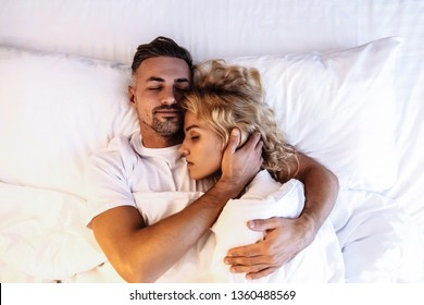 Couple. Love. Togetherness. Man and woman are hugging while sleeping in the bed; top view