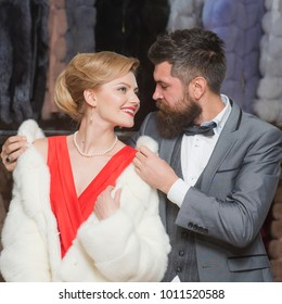Couple in love tries expensive mink overcoats on. Rich fashion concept. Guy with beard and woman buy furry coat.