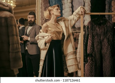 Couple in love tries expensive mink overcoats on. Rich fashion concept. Man and girl with seductive faces at clothes rack background. Guy with beard and woman buy furry coat.