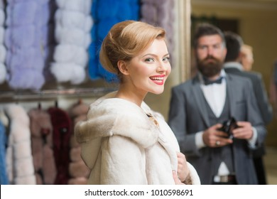 Couple in love tries expensive pink mink overcoat on. Man with wallet and girl with happy faces on clothes rack background. Customer with beard and woman buy furry coat. Elegance and glamour concept.