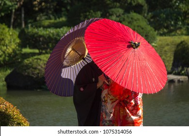 Couple in love with typical Japanese clothes and colorful umbrellas in a garden of Tokyo, Japan